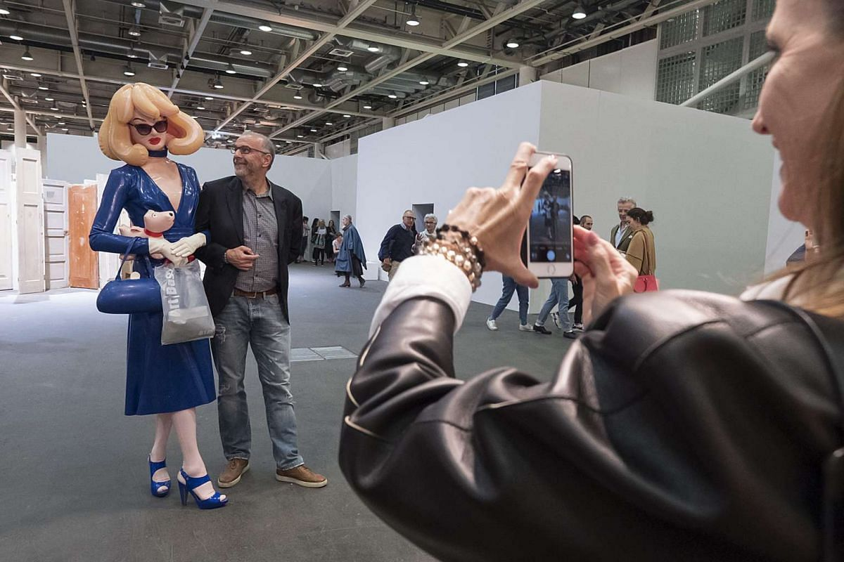 Pandemonia, the creation of an anonymous London-based artist, poses with a visitor at the show Unlimited of the international art show Art Basel, in Basel, Switzerland on June 16, 2016.
