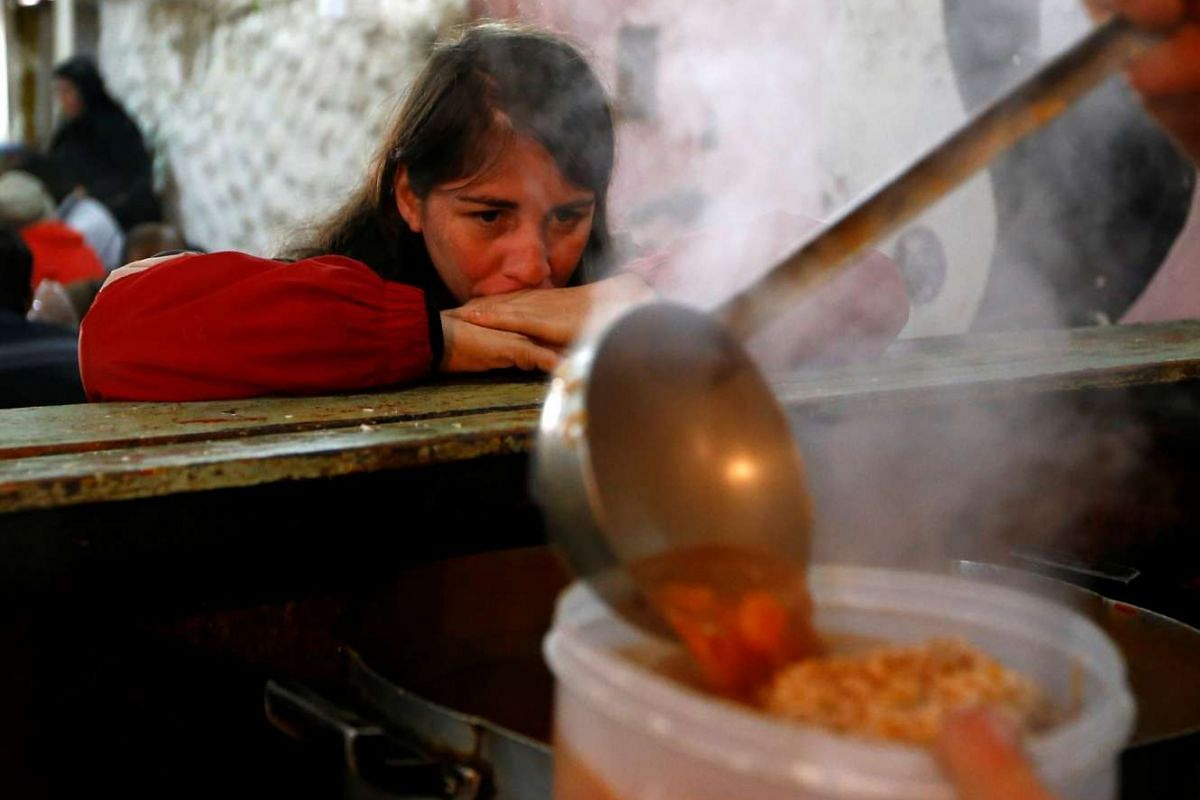 A woman waits for food at the Bokitas free community soup kitchen in a neighbourhood of Buenos Aires, Argentina on June 10, 2016.