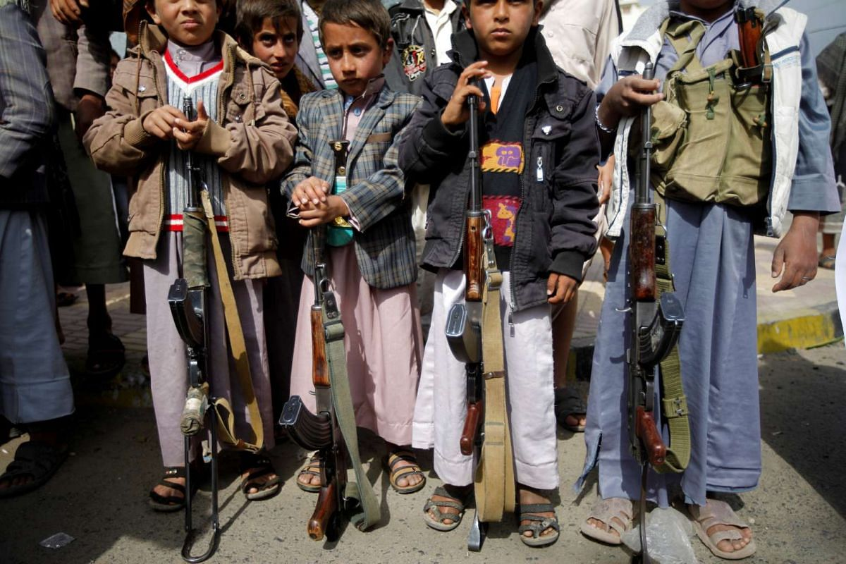 Boys holding weapons during a demonstration against the removal of the Saudi-led coalition from the United Nations annual child rights blacklist, outside the United Nations offices in Sanaa, Yemen on June 16, 2016.