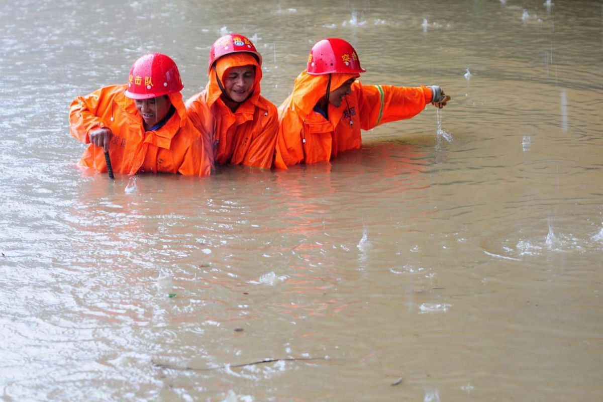 Workers trying to open a sewage well on a flooded road in Jiujiang, Jiangxi Province, China, on June 19, 2016. A week of torrential rain in southern China has killed dozens of people and forced relocation of tens of thousands of residents, media repo