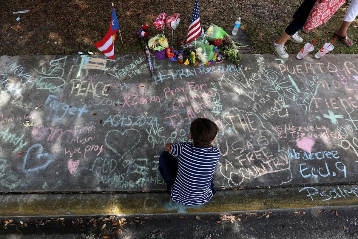 A child draws on the sidewalk in chalk at a makeshift memorial that is across the street from Pulse night club following last week's shooting in Orlando, Florida, on June 19, 2016.