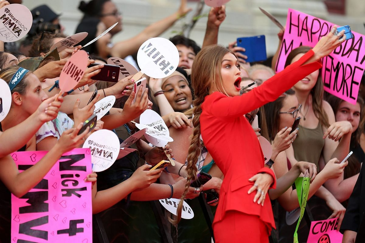 Model Gigi Hadid, who is hosting MMVA, takes pictures with fans as she arrives for the iHeartRadio Much Music Video Awards in Toronto, Ontario, Canada on June 19.
