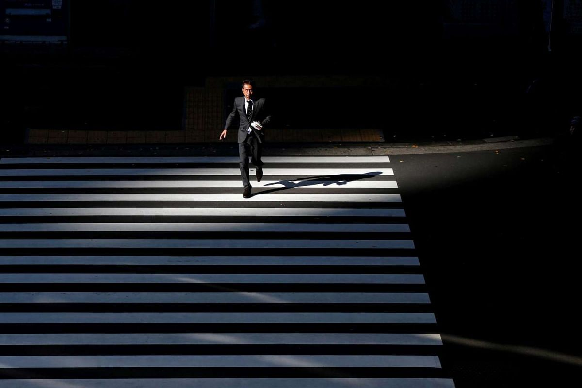 A businessman crosses a road at Tokyo's business district, in Japan, on Jan 20, 2016.