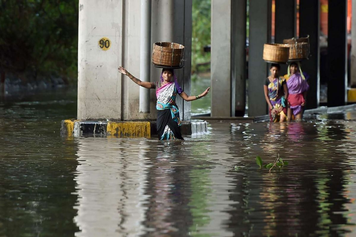 Indian pedestrians balance baskets on their heads as they wade through a flooded street after heavy monsoon rain showers in Mumbai, on June 21, 2016.