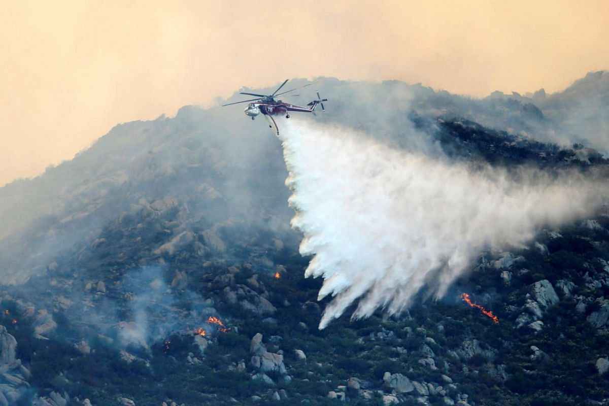 Firefighters use air assets to battle a wildfire as it burns in the hills near Potrero California, on June 20, 2016.