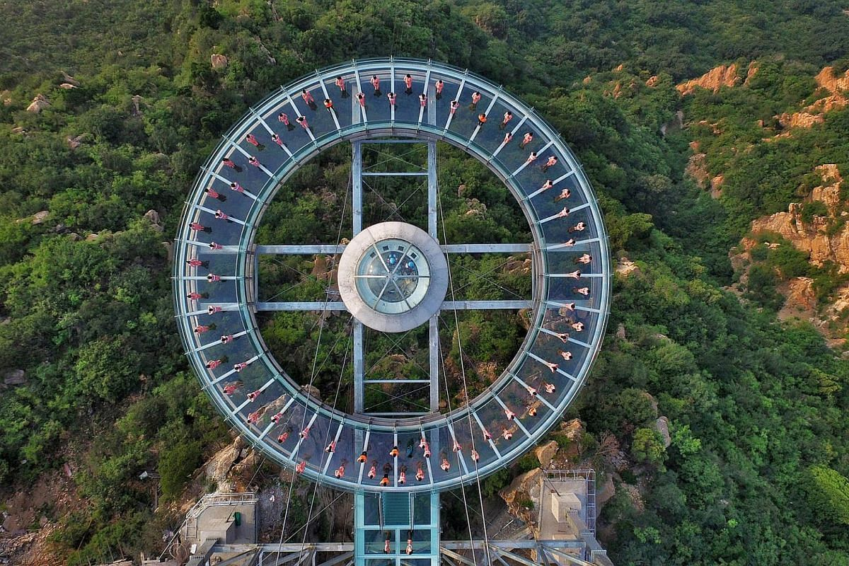 People practicing yoga on a glass sightseeing platform ahead of the International Day of Yoga, on the outskirts of Beijing, China, on June 20.