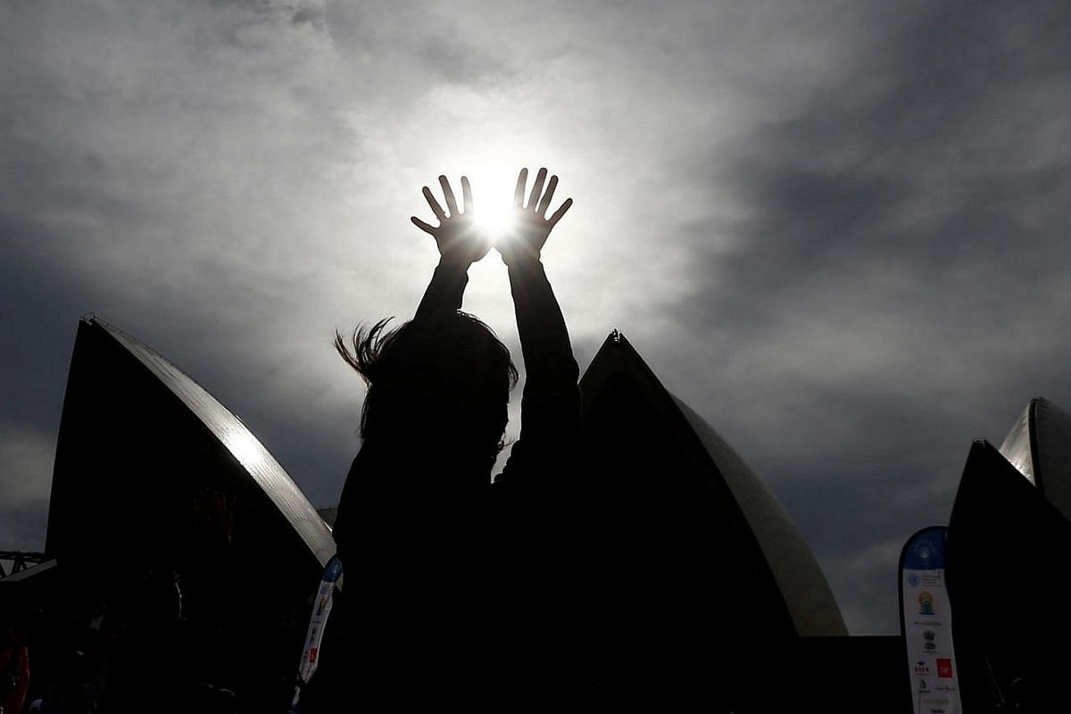 A yoga participant reaches to the sky in front of the Sydney Opera House on World Yoga Day in Sydney, Australia, on June 21.