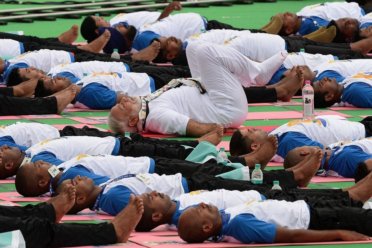 India's PM Narendra Modi (center) participates in a mass yoga session along with other yoga practitioners to mark the 2nd International Yoga Day at Capitol Complex in Chandigarh  on June 21.