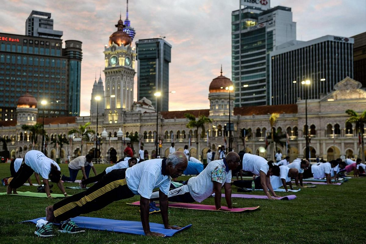 Practitioners perform yoga exercises during an event to mark International Yoga Day at the iconic Sultan Abdul Samad building in Kuala Lumpur, Malaysia, on June 21.