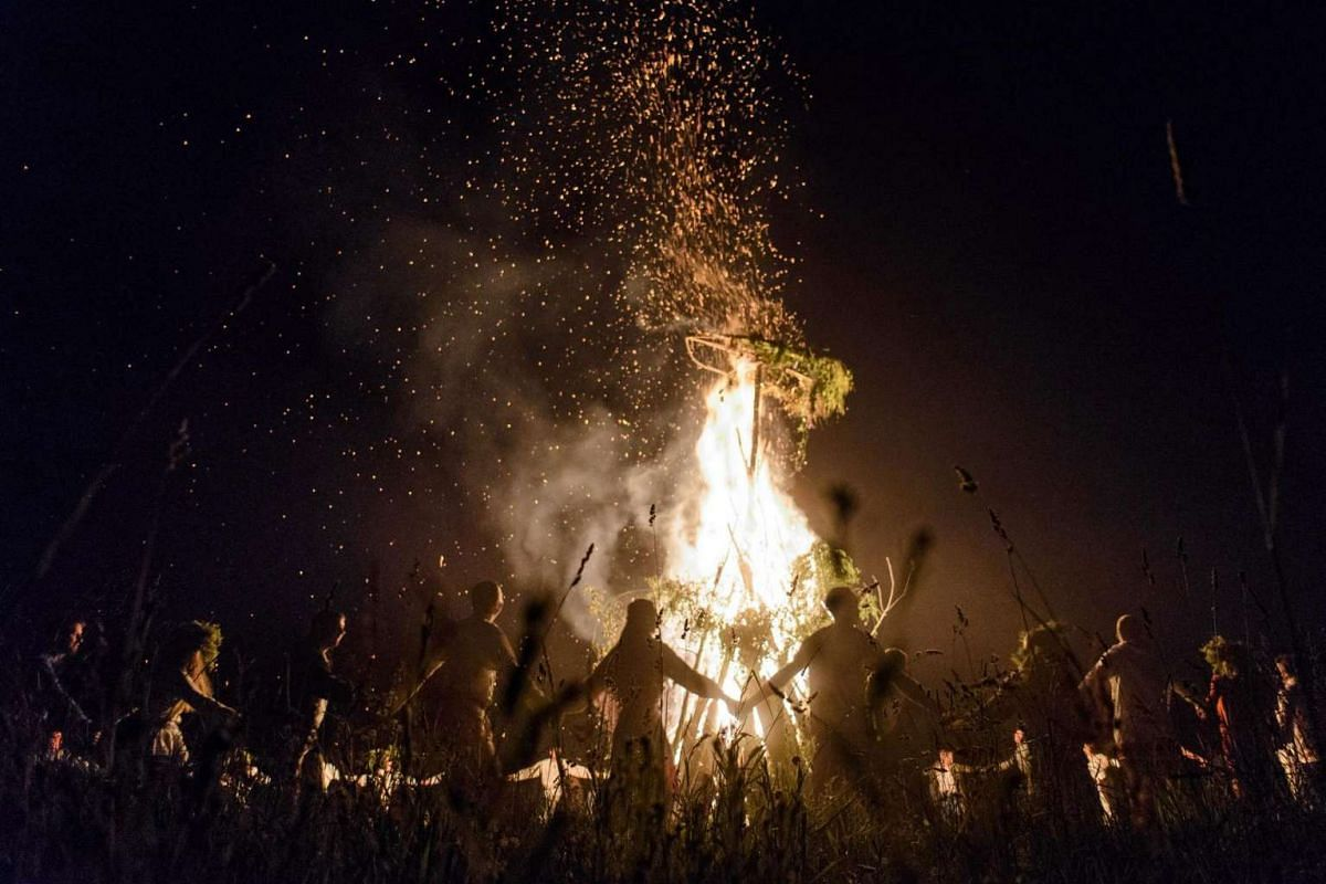 Young people wearing Belarus traditional clothes and wreaths dance around a bonfire as they celebrate the Ivan Kupala night, an ancient heathen holiday, held in the countryside near Minsk, on June 19, 2016.