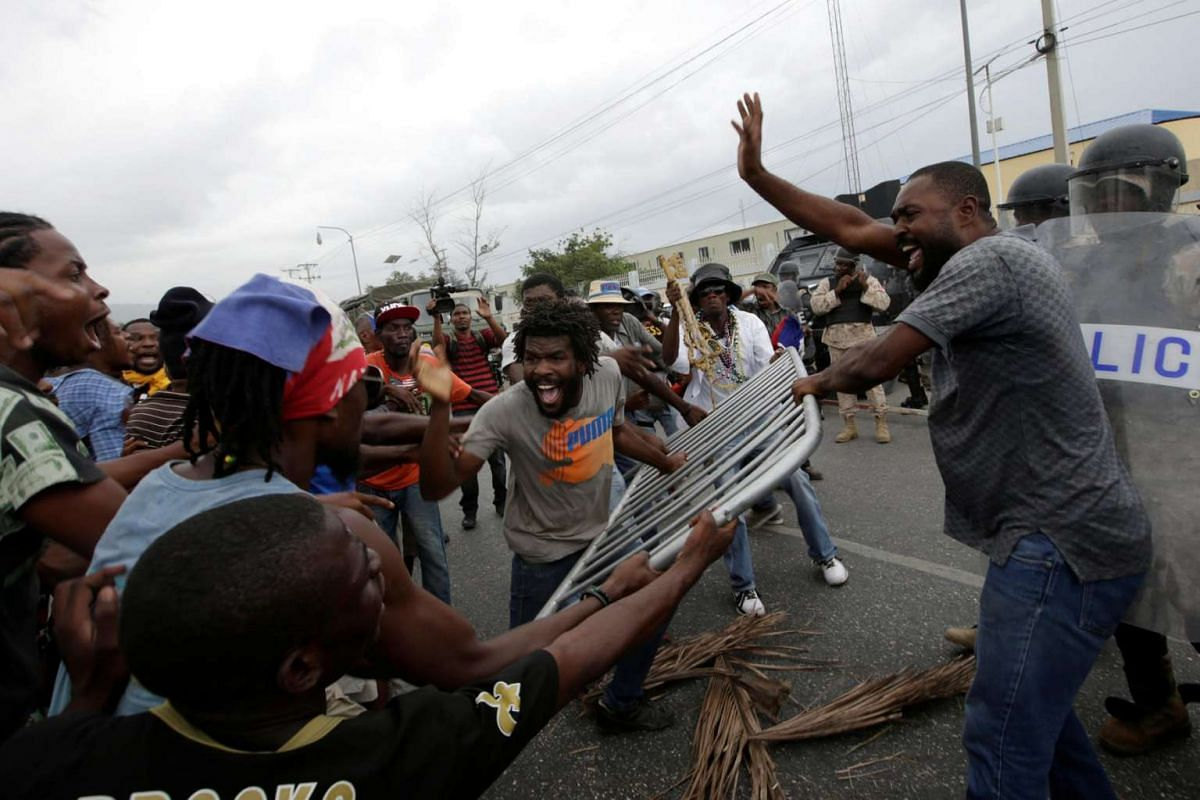 Supporters of Fanmi Lavalas political party in Haiti argue as some try to give back a fence to the National Police officers during a demonstration on June 21, 2016.