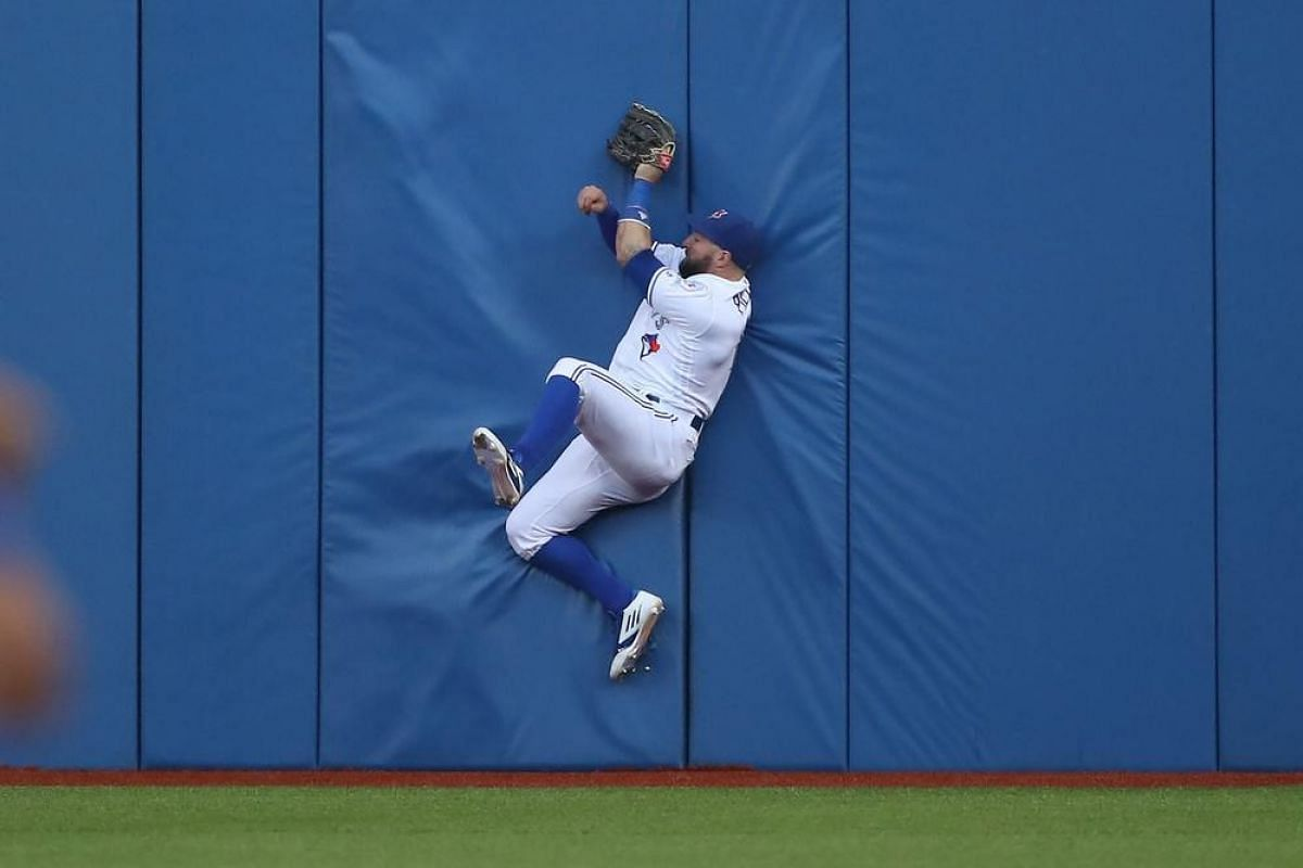 Kevin Pillar #11 of the Toronto Blue Jays catches a fly ball against the wall in the fourth inning during a match against the Arizona Diamondbacks on June 21, 2016.