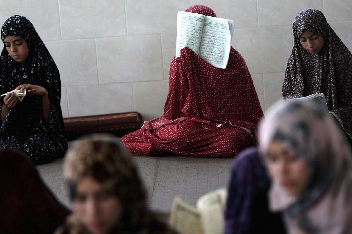 Palestinian girls reading the holy Quran during the fifteenth day of the holy month of Ramadan in Khan Younis town on June 21, 2016.