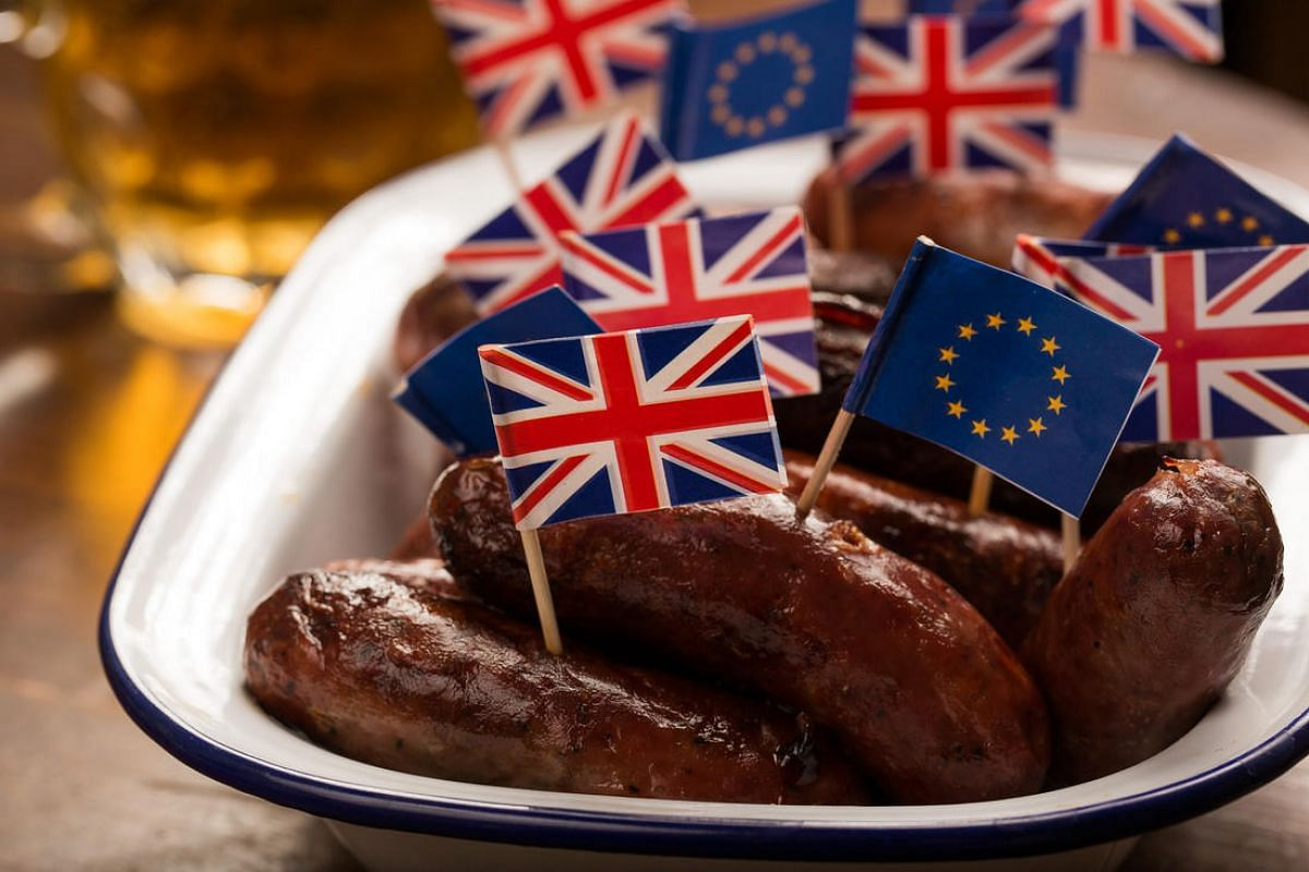 British Union Flags, commonly known as Union Jacks, and European Union (EU) flags stand on cocktail sticks in a dish of sausages on a table in Guildford, Surrey, on May 31, 2016.