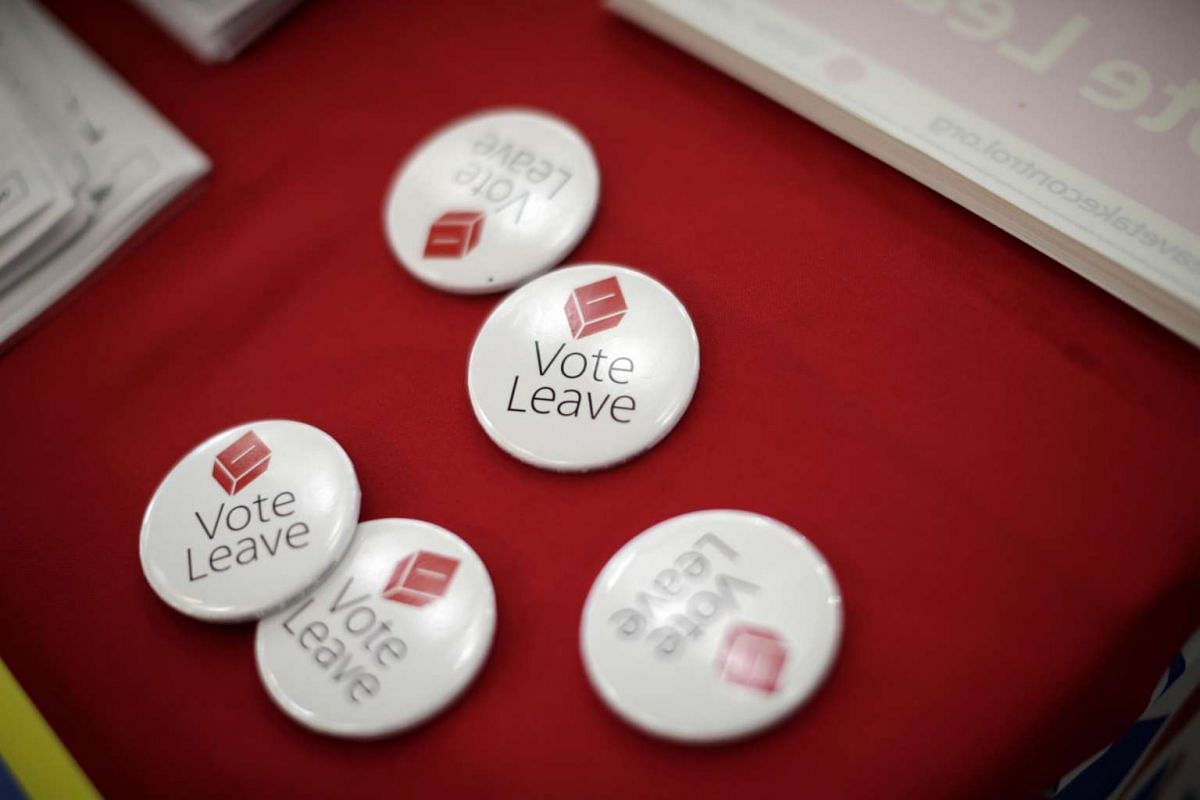 """""""Vote Leave"""" badges sit on a table with leaflets and other campaign materials in Manchester, on June 11, 2016."""