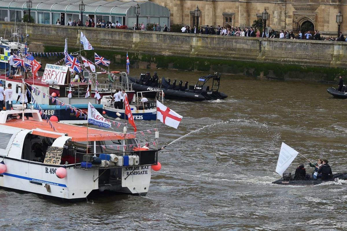 """A boat carrying supporters of """"IN"""" is sprayed with water by a flotilla of fishing trawlers, orgainsed by UKIP leader Nigel Farage, as it sails up the river Thames next to the Houses of Parliament in London, on June 15, 2016."""