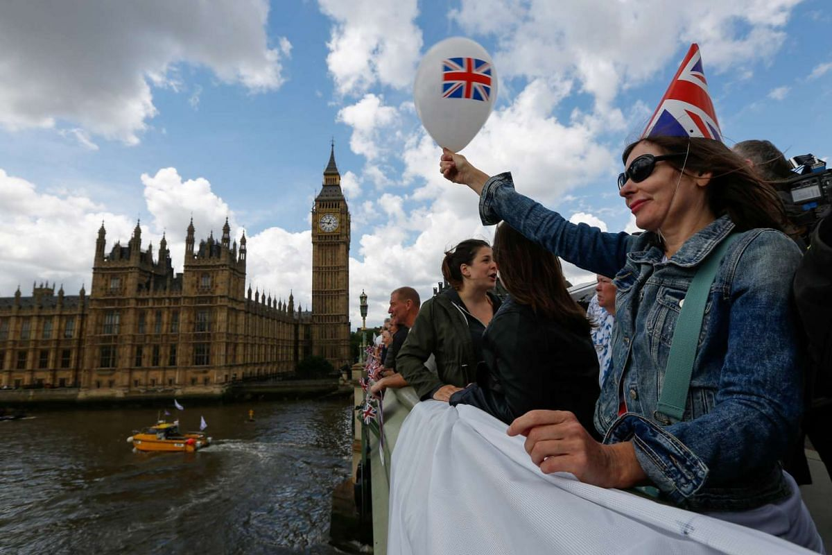 A campaigner waves a balloon featuring a British Union Flag, also known as a Union Jack, as boats pass underneath Westminster Bridge near the Houses of Parliament in London, on June 15, 2016.