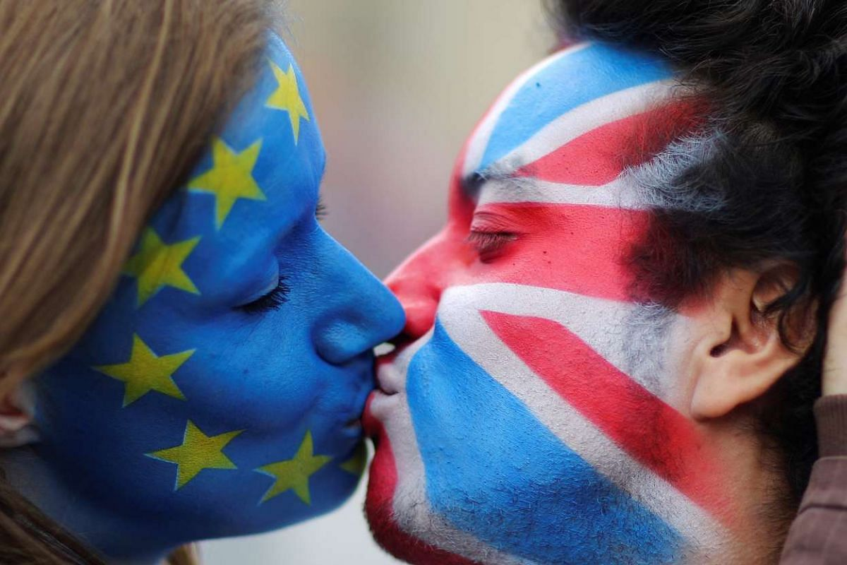 Two activists with the EU flag and Union Jack painted on their faces kiss each other in front of Brandenburg Gate to protest against the British exit from the European Union, in Berlin, June 19, 2016.