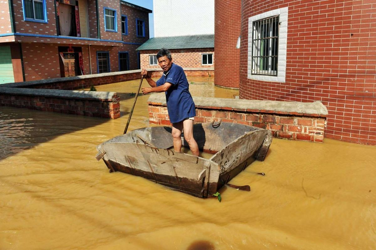 This photo taken on June 21, 2016 shows a resident making his way through a flooded area in a village in Poyang county, in southeast China's Jiangxi province.