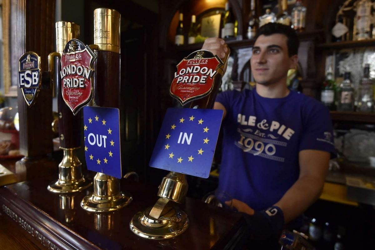 A bartender pulls a pint of beer decorated with EU Referendum beer taps in a pub in central London, on June 22, 2016.