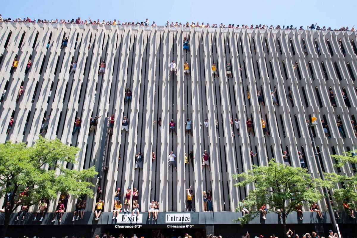 Fans scale the side of a parking garage to get a better view during the Cleveland Cavaliers 2016 championship victory parade and rally on June 22, 2016 in Cleveland, Ohio.