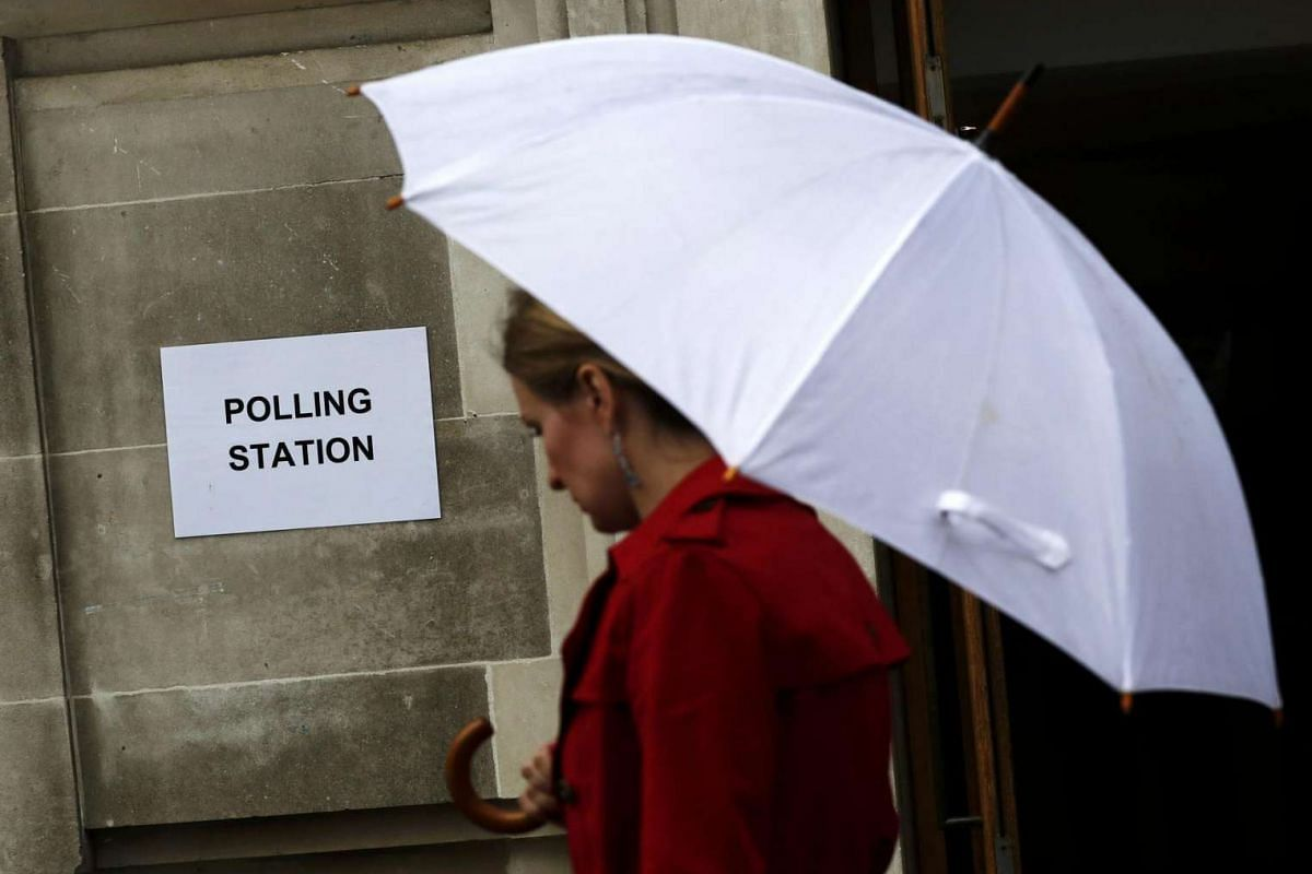A woman carries an umbrella past a polling station in north London on June 23, 2016.