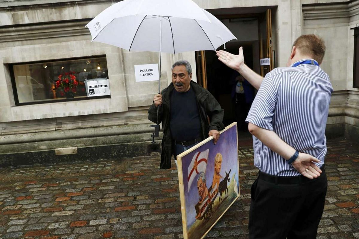 A man carries a painting outside a polling station in north London on June 23, 2016.