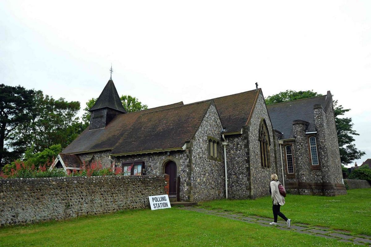 A woman arrives to cast her vote at the Parish church of St Peter in West Blatchington, near Brighton in southern England, on June 23, 2016.