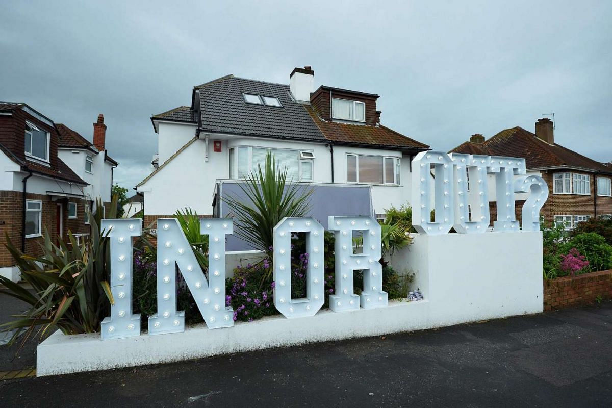 """An illuminated """"In or Out"""" sign is pictured outside a house in Hangleton, near Brighton in southern England, on June 23, 2016."""