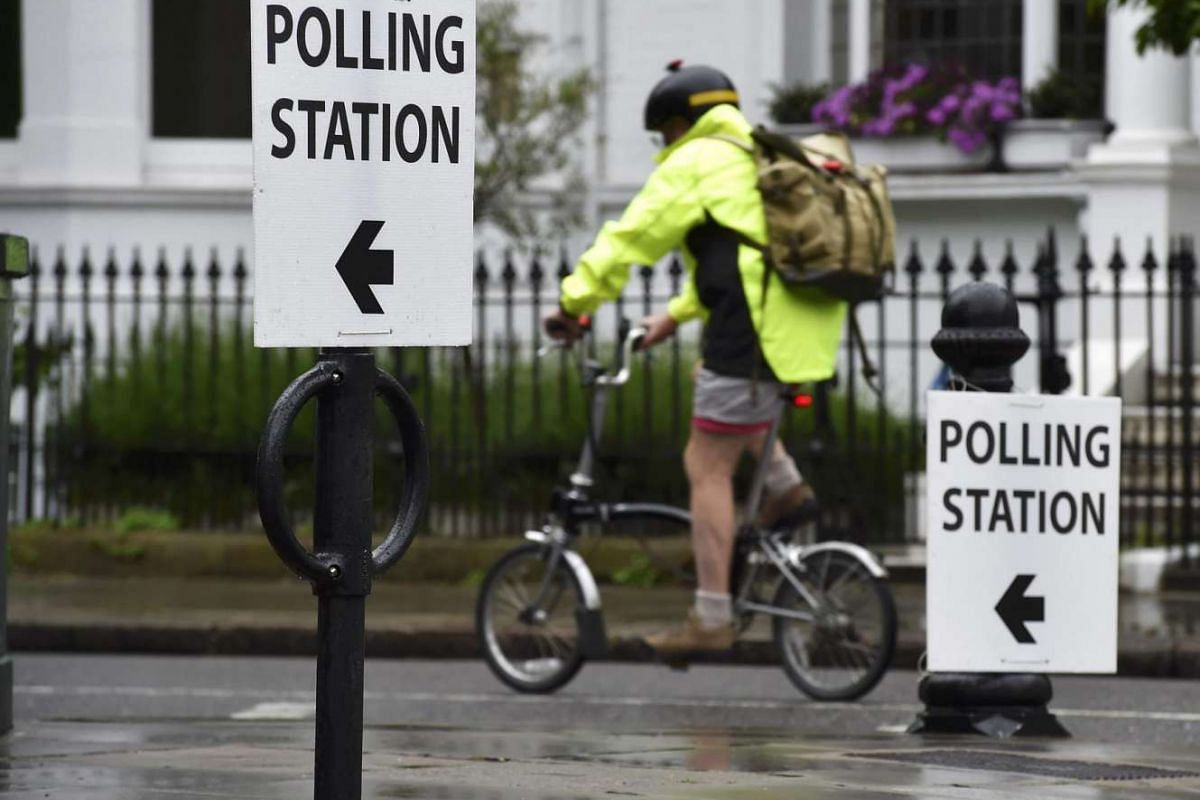 A man cycles past a polling station in west London on June 23, 2016.