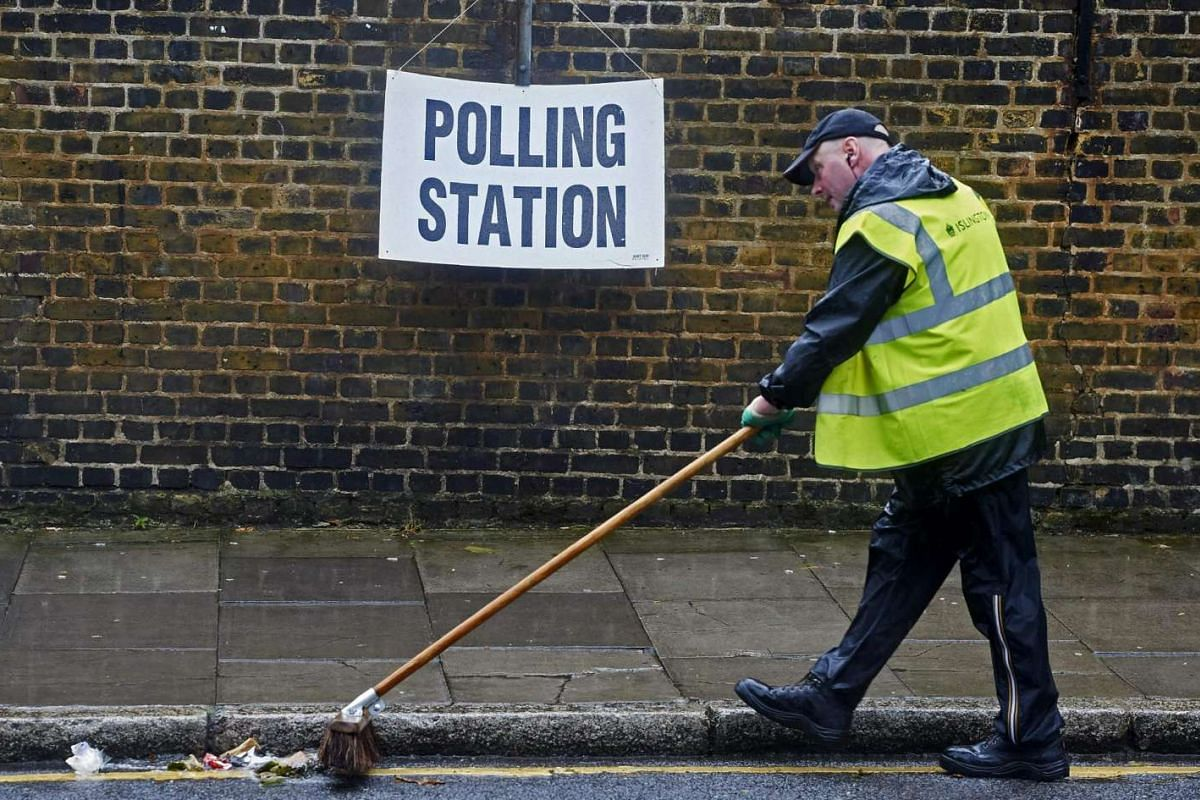 A worker sweeps rubbish in the road near a polling station sign in London on June 23, 2016.