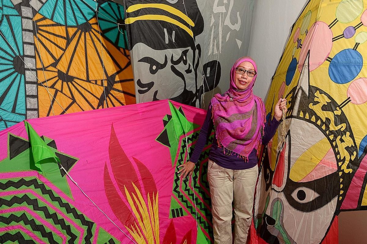 Ms Widiyati posing with some of her kites. Her designs have evolved from simple, traditional ones to those that are more creative, including inflatable kites. She spends up to a few months making them.