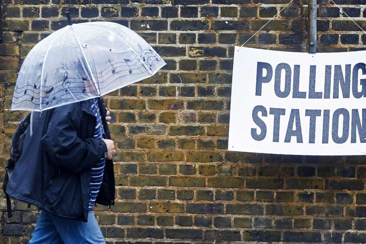 A man shelters from the rain as he arrives at a polling station in London on June 23, 2016.