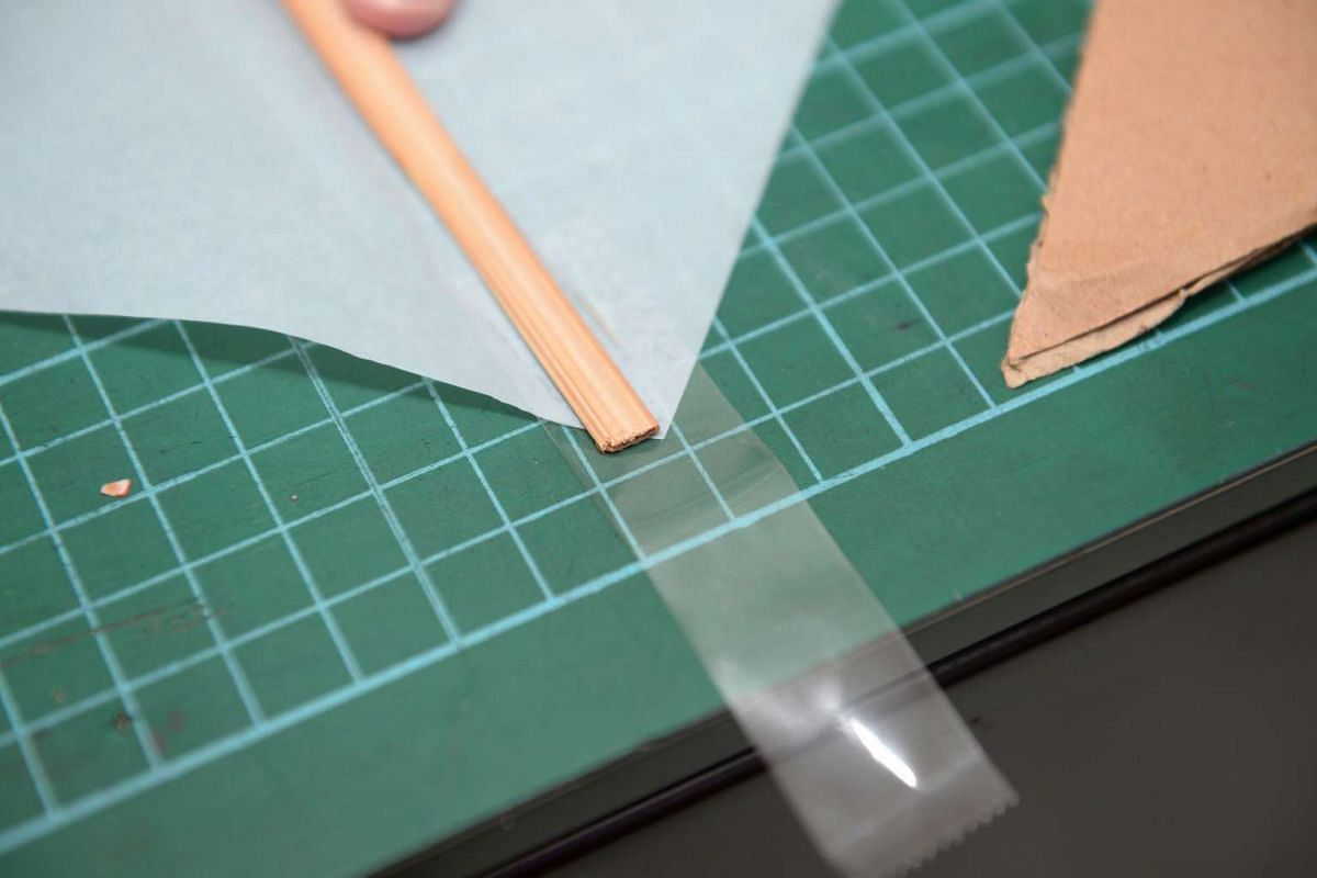 HOW TO MAKE A KITE: 2. Place tape (50mm) on four corners – half on sail, half outside.