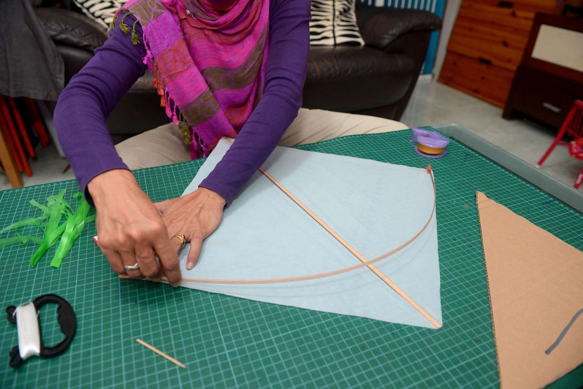 HOW TO MAKE A KITE: 3. Place short bamboo vertically  in the centre, fold tape into sail.