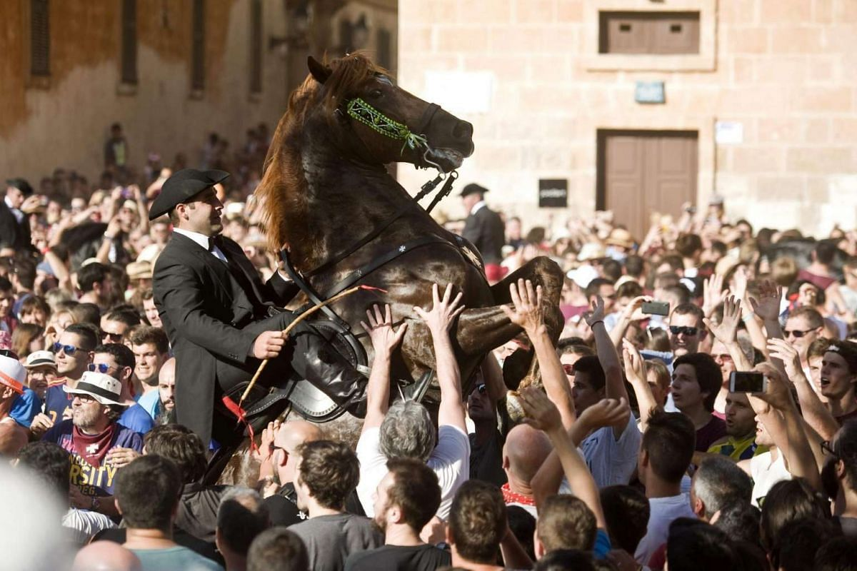 A man in costume rides a horse to the Born Square during St John's Eve celebrations in Ciutadella, Menorca, Balearic Islands, on June 23, 2016. St John's Eve is a celebration that falls before the observed birthday of St John the Baptist.