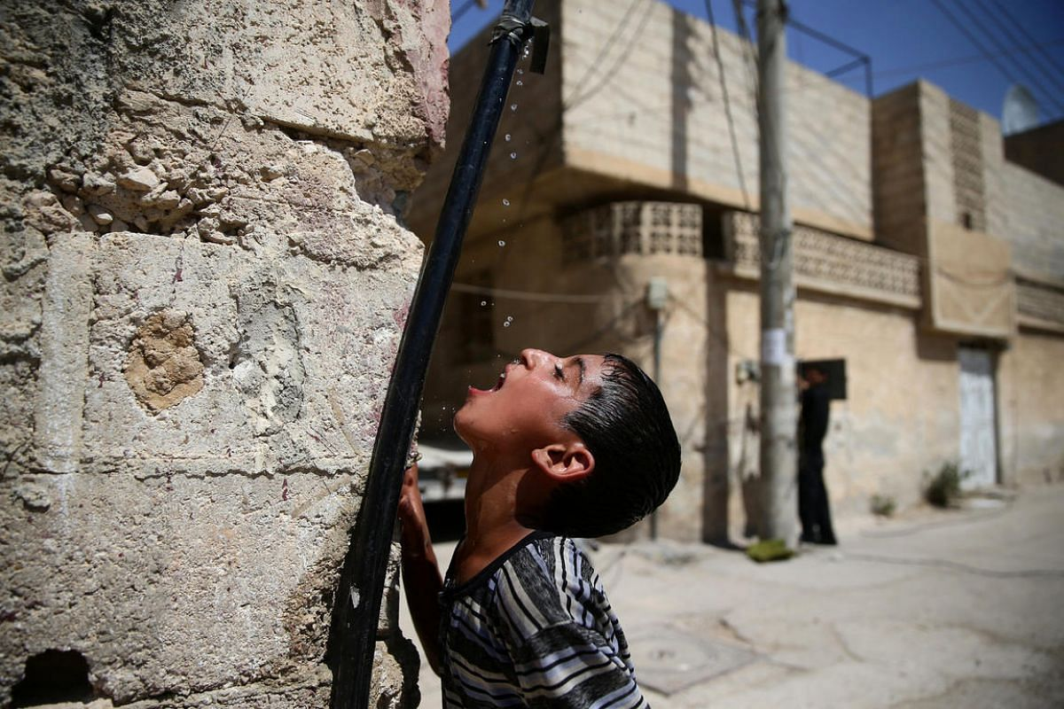 A boy drinks water from a pipe, in the rebel-held besieged town of Douma, eastern Damascus suburb of Ghouta, Syria, on June 23, 2016.