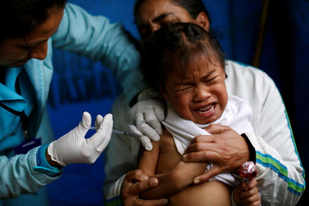 A girl is vaccinated against influenza during a vaccination campaign in Lima, Peru, on June 23, 2016.