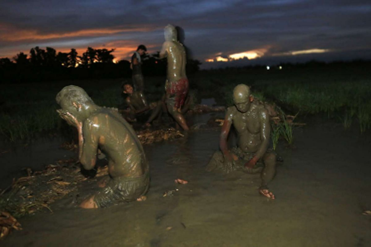 Devotees cover their body with mud before a holy mass to mark the 'Taong Putik' (Mud People) Festival on June 24, 2016.