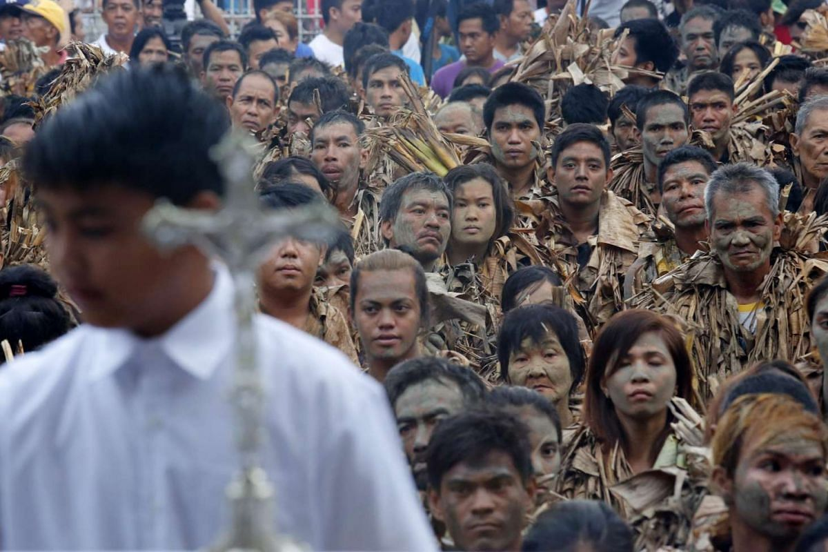 Devotees covered in mud and dressed in dried leaves, attend a holy mass to mark the 'Taong Putik' (Mud People) Festival on June 24, 2016.
