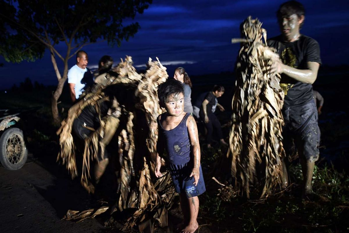 A family of devotees covered in mud and dressed in dried leaves, attend a holy mass to mark the 'Taong Putik' (Mud People) Festival on June 24, 2016.