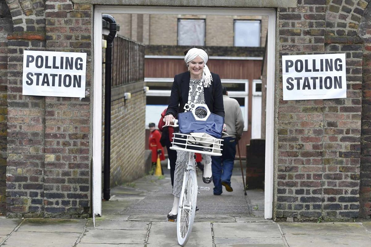 A woman cycles out of a polling station for the Referendum on the European Union in Chelsea, London, Britain, on June 23, 2016.