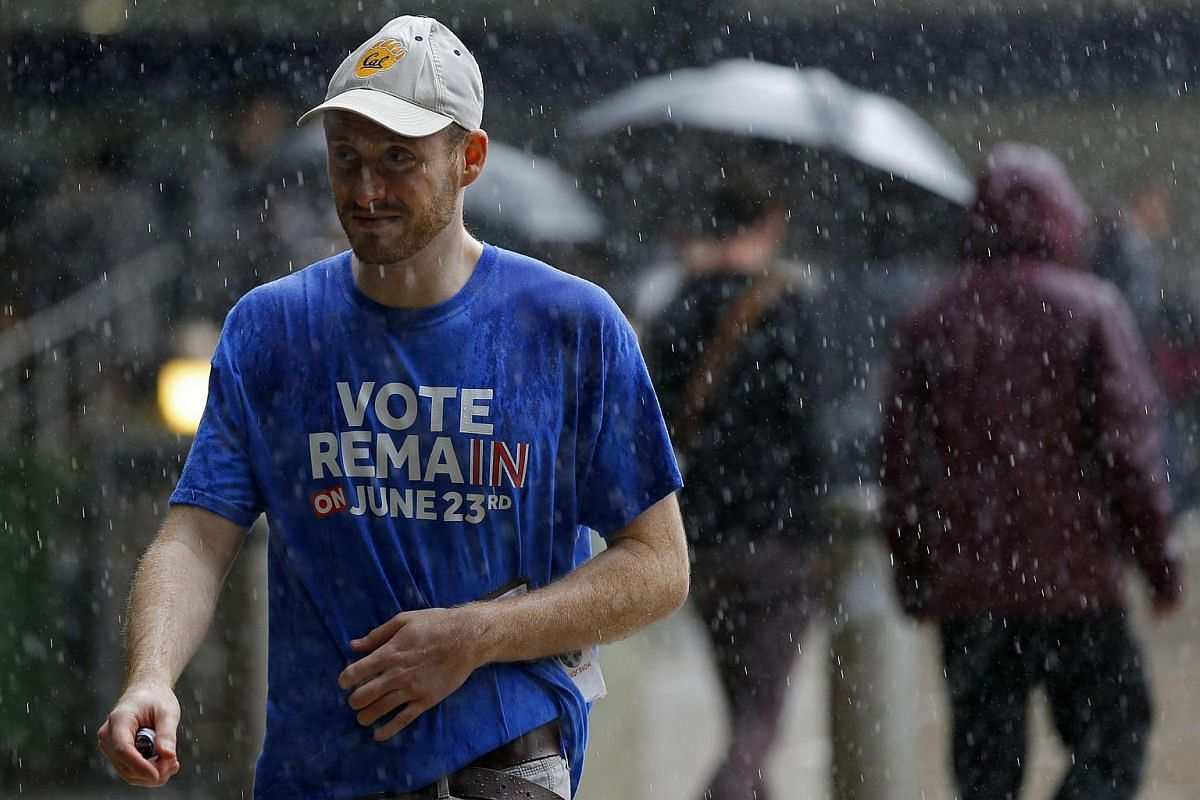 """A man wearing a """"Vote Remain"""" T-shirt walks in the rain in central London on June 23."""