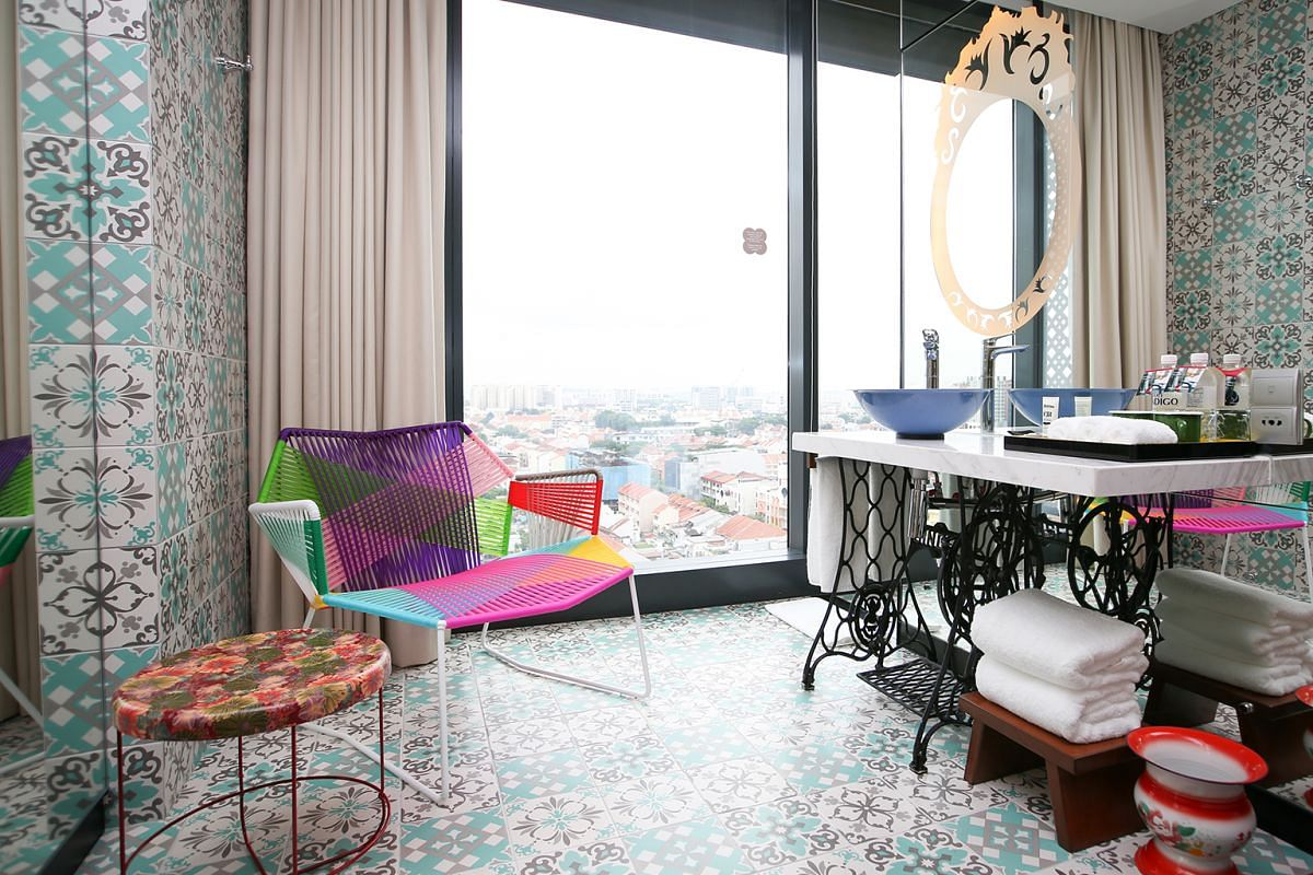In Hotel Indigo Singapore Katong, a Singer sewing machine base props up the vanity counter and basin in the bathroom, which is also furnished with traditional items such as a spittoon.