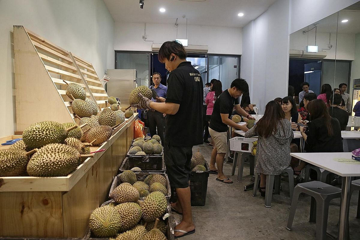 Durian vendors say supplies of the fruit have shrunk by 30 to 50 per cent compared with last year, but at shops such as Ministry Of Durian (above), customers are still feasting on the fruit.