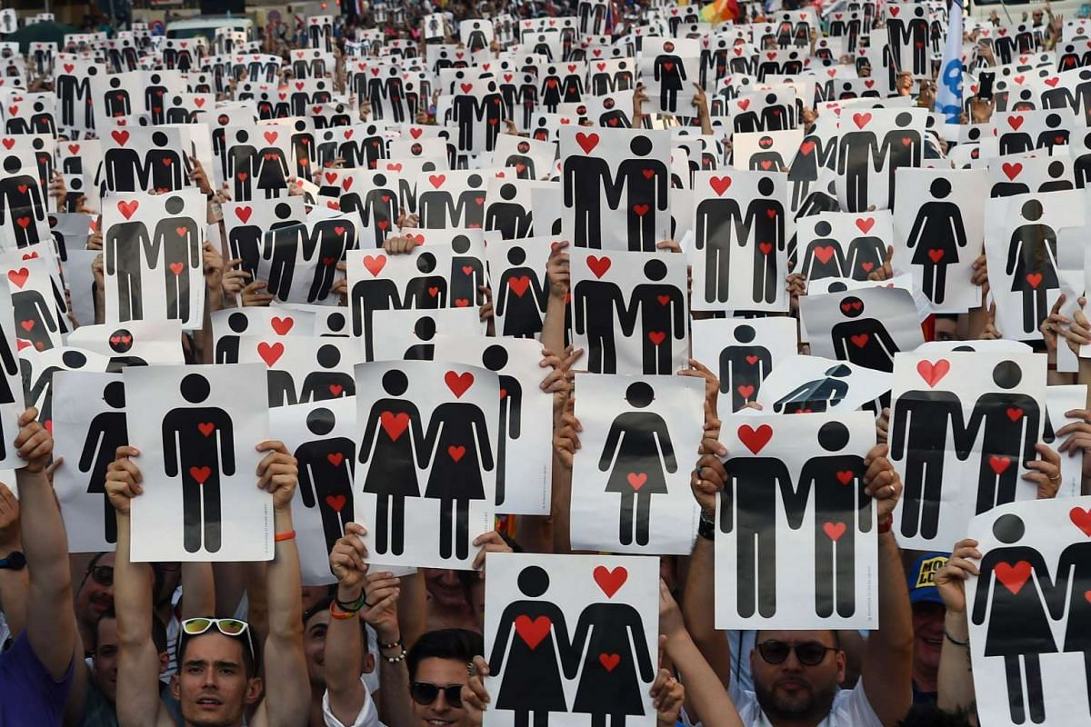 People hold placards depicting hearts and couples during a flash mob for the annual Lesbian, Gay, Bisexual and Transgender (LGBT) Pride Parade in Milan on June 25, 2016.
