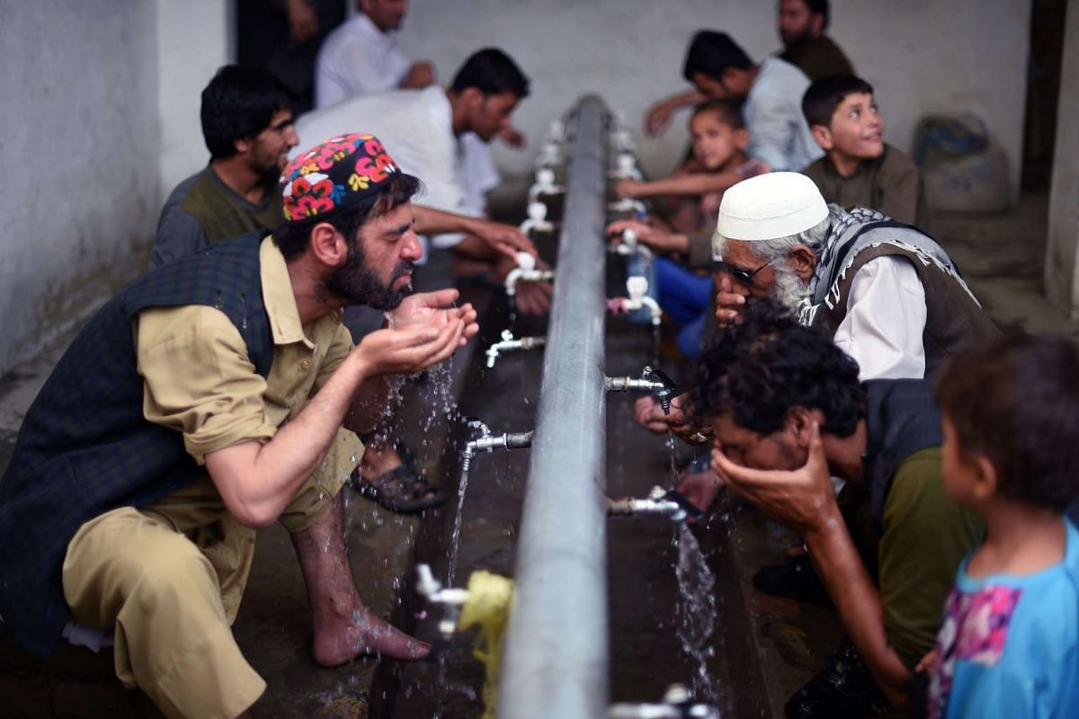 Afghan Muslims wash before attending prayers during the month of Ramadan on June 26, 2016.