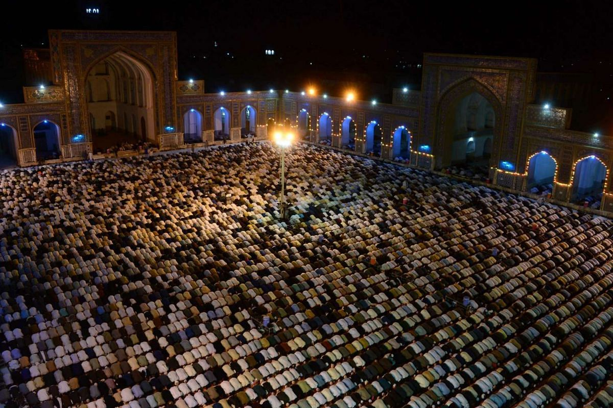 """Afghan devotees perform a special evening """"Taraweeh"""" prayer during the month of Ramadan on June 25, 2016."""
