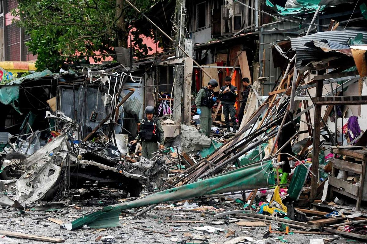 Members of a Thai bomb squad inspect the site of a car bomb blast triggered by suspected separatist militants in Narathiwat on June 26, 2016.