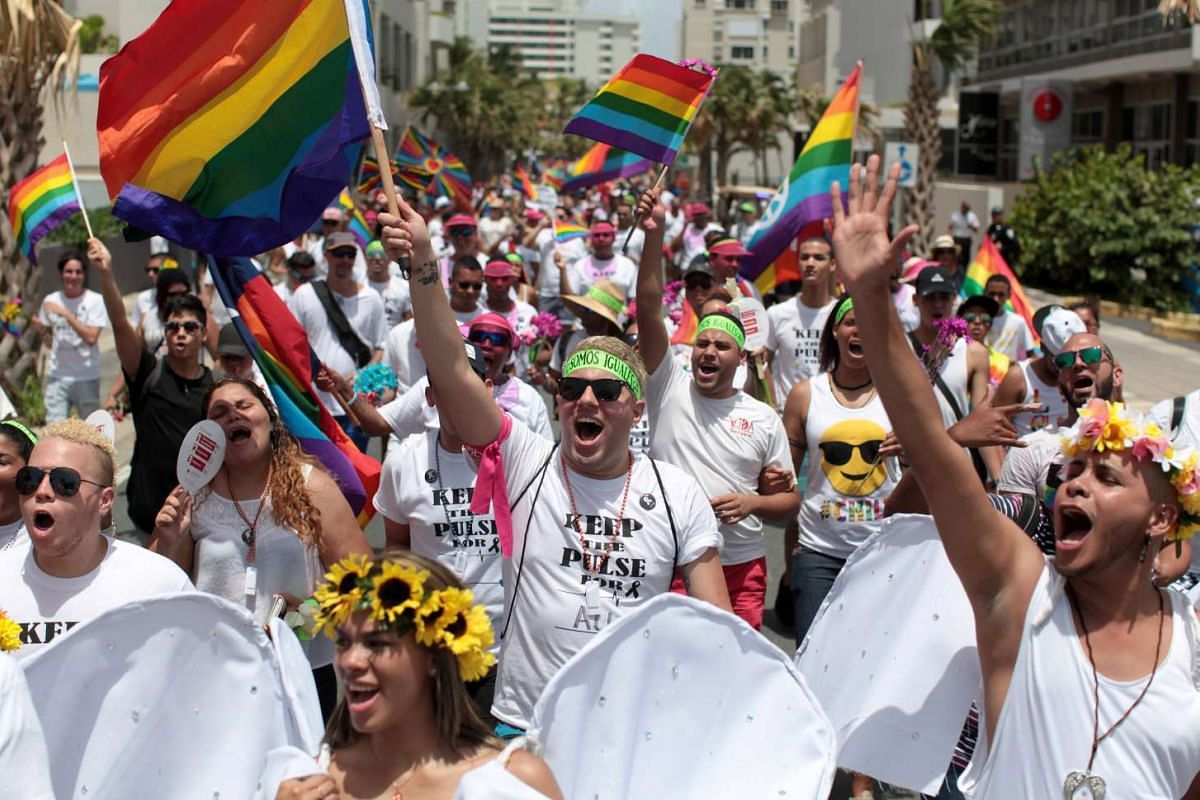Participants wear T-shirts printed with a tribute to the victims of the Orlando shooting during the annual gay pride parade in San Juan, Puerto Rico on June 26, 2016.